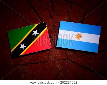 Saint Kitts And Nevis Flag With Argentinian Flag On A Tree Stump Isolated