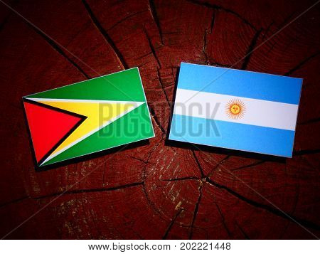 Guyana Flag With Argentinian Flag On A Tree Stump Isolated