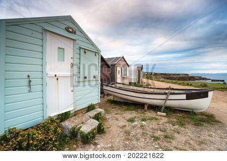 Beach huts and a boat under a moody sky at Portland Bill near Weymouth on the Dorset coast