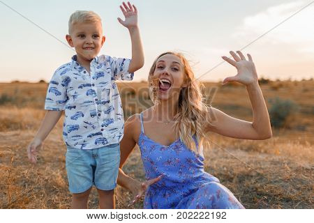 A photo of a handsome boy and his mom showing their palms on a nature background. A happy blond child and pretty mother playing in the outdoors. Family, kid and parenthood concept. Copy space.