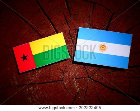 Guinea Bissau Flag With Argentinian Flag On A Tree Stump Isolated