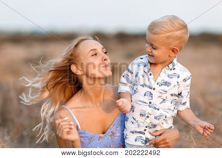 A close-up photo of a charming, happy mother and her little child playing with each other on a blurred nature background. Delighted, smiling young mom with a little baby boy on a yellow field.