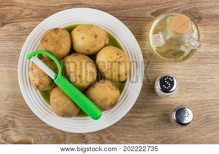 Raw Potatoes And Peeler In Plate, Oil, Salt And Pepper