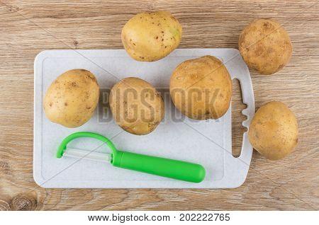 Raw Unpeeled Potatoes, Vegetable Peeler On Cutting Board On Table