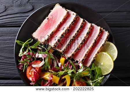 Beautiful Food: Steak Tuna In Sesame, Lime And Fresh Salad Close-up On A Plate. Top View Horizontal