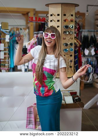 A portrait of a smiling happy girl standing in a shopping center and trying on white stylish sunglasses. A shopaholic on a blurred shop background. Summer accessories. Shopping, fashion concept.