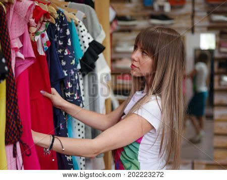 A close-up portrait of a young woman on a blurred background. A fashionable female choosing herself a beautiful stylish dress in a clothing store. Shopping, consumerism concept. Copy space.