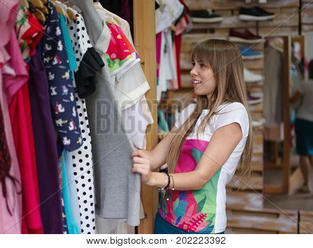 A fashionable female choosing herself a beautiful stylish dress in a clothing store. A portrait of a young woman on a blurred background. Shopping, consumerism, fashion concept. Copy space.