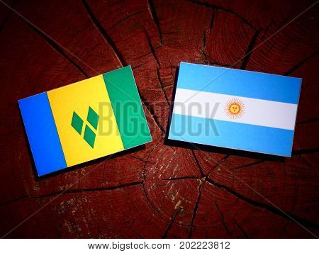 Saint Vincent And The Grenadines Flag With Argentinian Flag On A Tree Stump Isolated