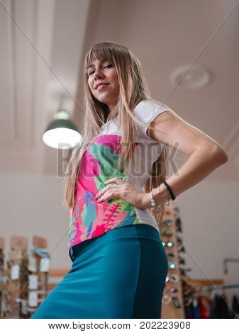 A close-up portrait of a fashionable girl posing on a shopping store background. A beautiful young woman in a stylish turquoise skirt and colorful brand T-shirt. Fashion, beauty, shopping concept.