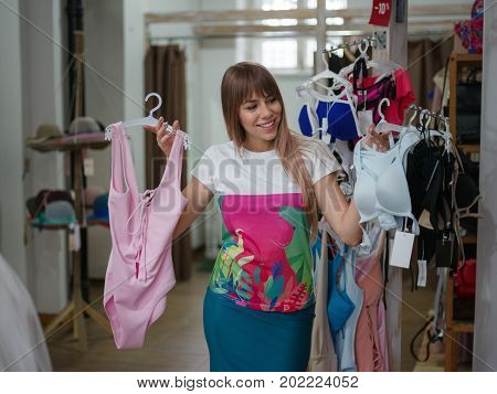A close-up portrait of a young woman on a blurred background. A female choosing herself a beautiful sexy colorful swimsuit in a clothing store. Shopping, fashion, beauty concept. Copy space.