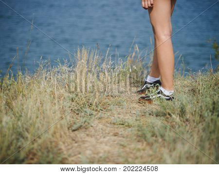 Close-up picture of fit, sporty woman's legs on a blurred natural background. A girl in snickers or suede shoes walking on a grassy hill. Camping, traveling, trip, journey concept. Copy space.