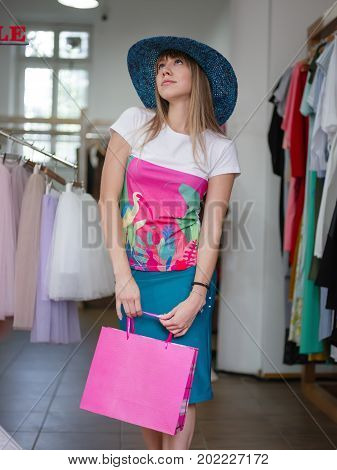 A portrait of a gorgeous woman wearing a colorful T-shirt, knee-length skirt, and blue broad-brimmed hat on a shop background. A satisfied lady with a shopping bag makes purchases in a big mall.