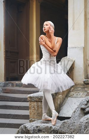 Beautiful young ballerina posing sensually outdoors standing on a stone near old building stairway embracing herself gently sensuality femininity tenderness concept.