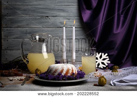 A healthy Christmas dessert with a lot of powder sugar and violet flowers on a plate and on a gray wooden background. A long lighted candles and drinks for traditional holidays dinner. Copy space.