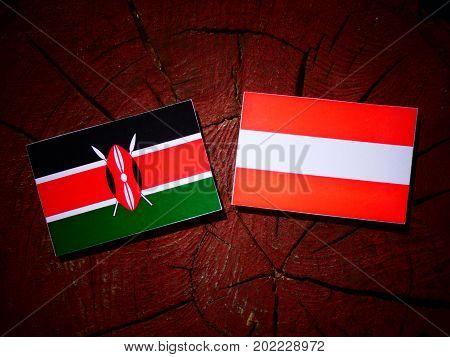 Kenyan Flag With Austrian Flag On A Tree Stump Isolated