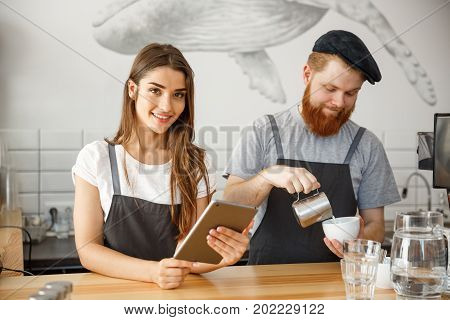 Coffee Business Concept - happy young couple business owners of small coffee shop working and planing on tablet.