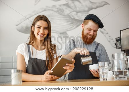 Coffee Business Concept - Cheerful baristas looking at their tablets for online orders in modern coffee shop.