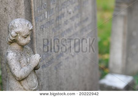 statue of a stone cherubim / angel in a cemetery in london, england poster