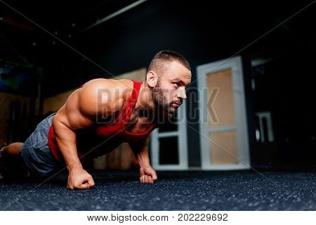 Close-up of a gorgeous sports man doing push-ups on a dark gym background. A professional bodybuilder exercising and building arm muscles. Fit male in comfortable sports clothes. Copy space.