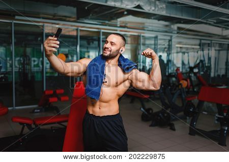 A gorgeous and muscular man flexing and showing off his arm muscles on a blurred gym background. A manly bodybuilder with blue towel, headphones and smartphone taking selfies of his hot, fit body.