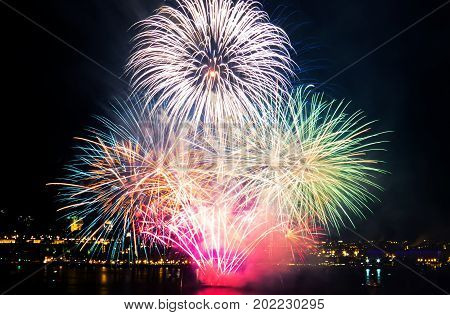 Very colorful fireworks over the Saint-Lawrence River with a part of Quebec city in the background. Quebec, Canada.