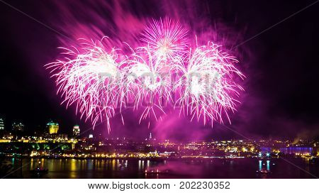 Very pink fireworks over the Saint-Lawrence River with a part of Quebec city in the background. Quebec, Canada.