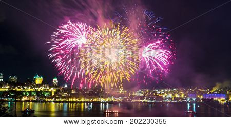 Orange and pink fireworks over the Saint-Lawrence River with a part of Quebec city in the background. Quebec, Canada.