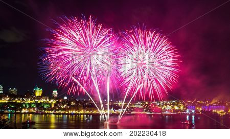Pink fireworks over the Saint-Lawrence River with a part of Quebec city in the background. Quebec, Canada.
