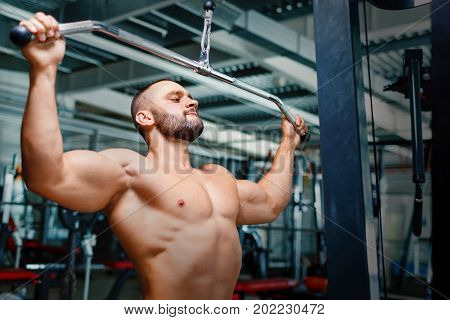 A perfect muscular young man with a six abs pack, biceps and triceps sitting on a blurred gym equipment background. A healthy attractive sports man working out on the arm press machine.