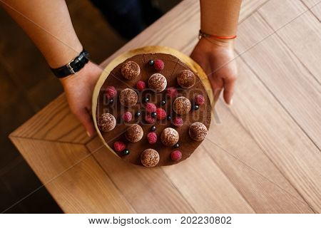 A view from above of woman's hands holding of a delicious chocolate cake with a creamy layer on a wooden background. A round cake with ripe raspberries and black currant on a top. Sweet snacks.