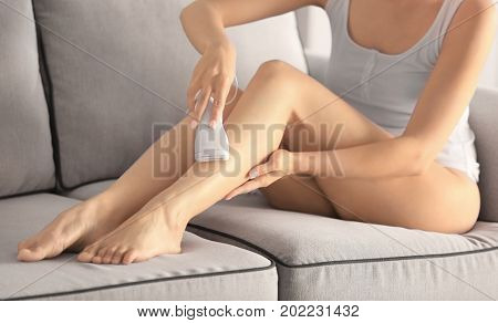 Beautiful young woman epilating legs while sitting on sofa at home