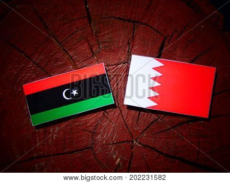 Libyan Flag With Bahraini Flag On A Tree Stump Isolated