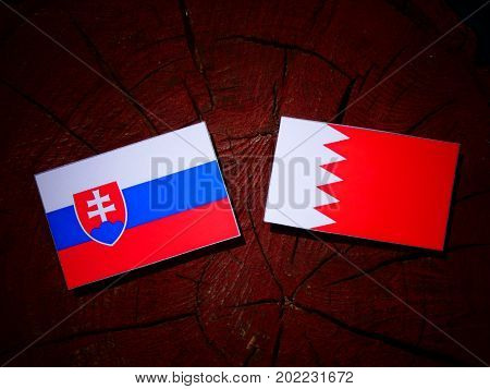 Slovakian Flag With Bahraini Flag On A Tree Stump Isolated