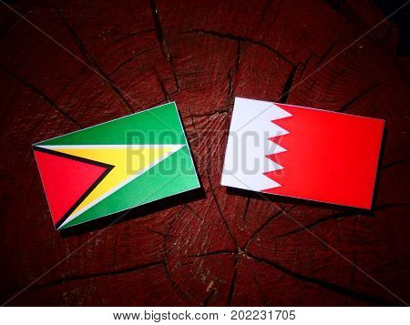 Guyana Flag With Bahraini Flag On A Tree Stump Isolated