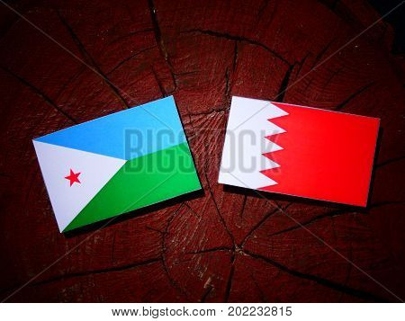Djibouti Flag With Bahraini Flag On A Tree Stump Isolated