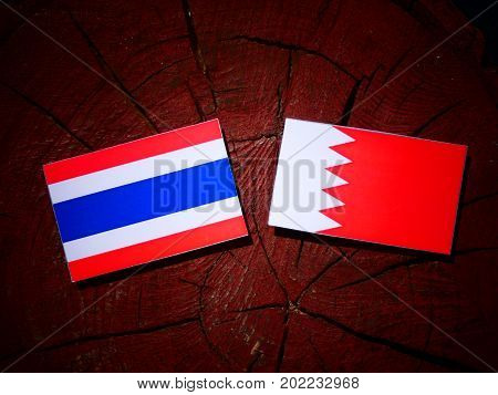 Thai Flag With Bahraini Flag On A Tree Stump Isolated