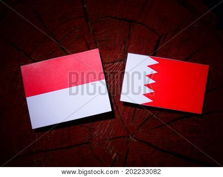 Monaco Flag With Bahraini Flag On A Tree Stump Isolated