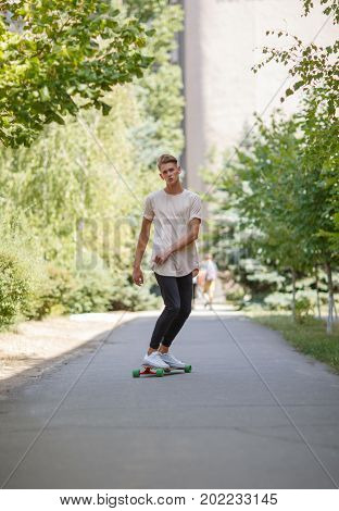 A skating boy. Full-length photo of a fashion young man in casual clothes on a skateboard on a blurred natural background. Action, skateboarding, motion, sport, and training concept.