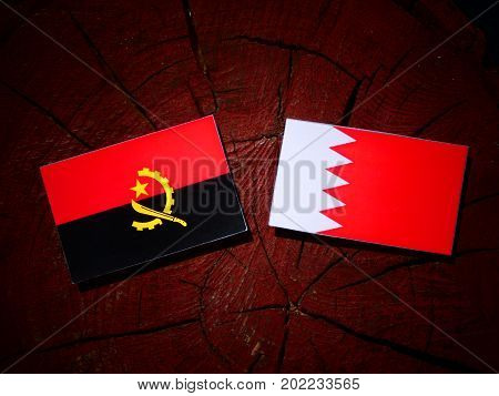 Angolan Flag With Bahraini Flag On A Tree Stump Isolated