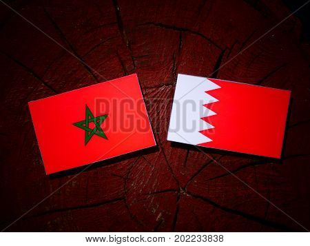 Moroccan Flag With Bahraini Flag On A Tree Stump Isolated