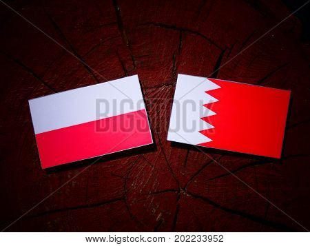 Polish Flag With Bahraini Flag On A Tree Stump Isolated