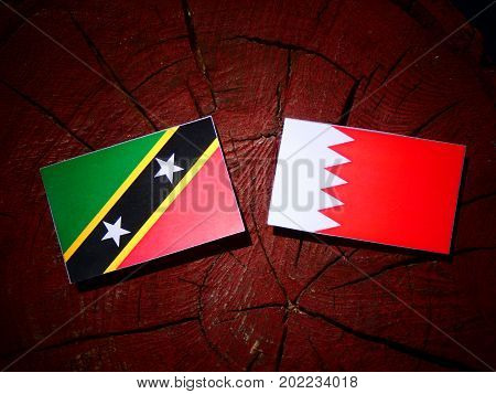 Saint Kitts And Nevis Flag With Bahraini Flag On A Tree Stump Isolated