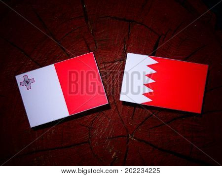 Maltese Flag With Bahraini Flag On A Tree Stump Isolated