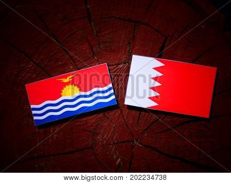 Kiribati Flag With Bahraini Flag On A Tree Stump Isolated