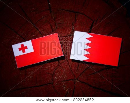 Tongan Flag With Bahraini Flag On A Tree Stump Isolated