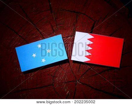 Micronesian Flag With Bahraini Flag On A Tree Stump Isolated