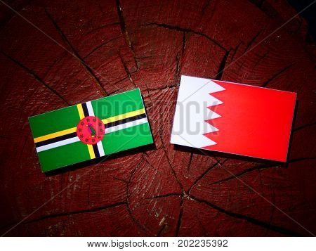 Dominica Flag With Bahraini Flag On A Tree Stump Isolated