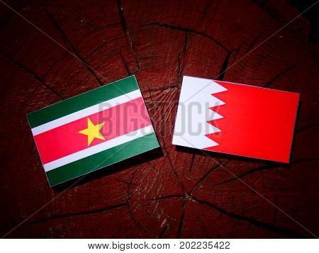 Suriname Flag With Bahraini Flag On A Tree Stump Isolated