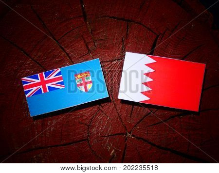 Fijian Flag With Bahraini Flag On A Tree Stump Isolated